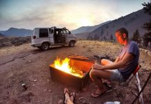 Two young people on a vanlife road trip, stay near a bonfire and a van, in a camp, surrounded by mountains.
